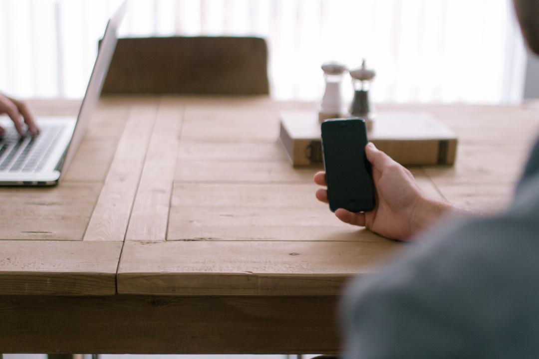tlf en la mano con mesa de trabajo